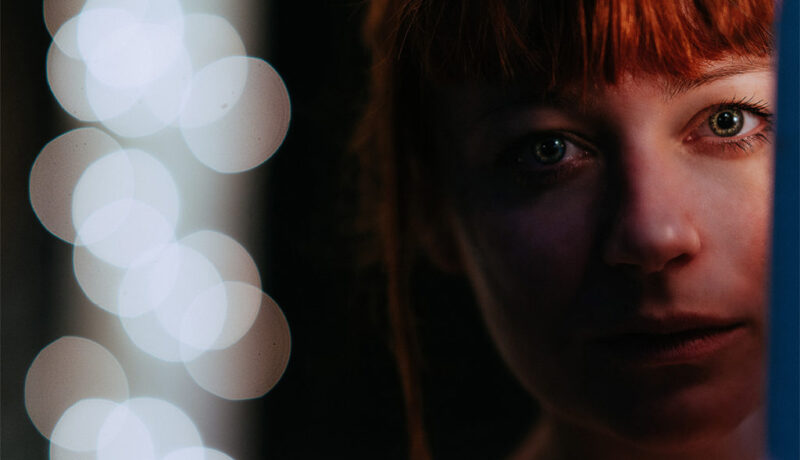 Cinematic close up of ginger woman with green eyes in the darkne